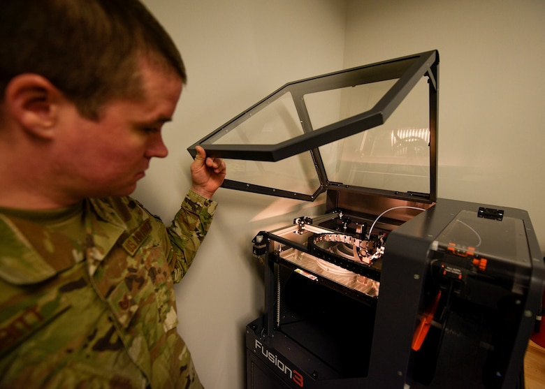An Airman opens the cover to a 3D printer.