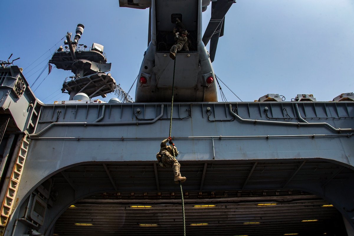 Marines rappel out of an aircraft.