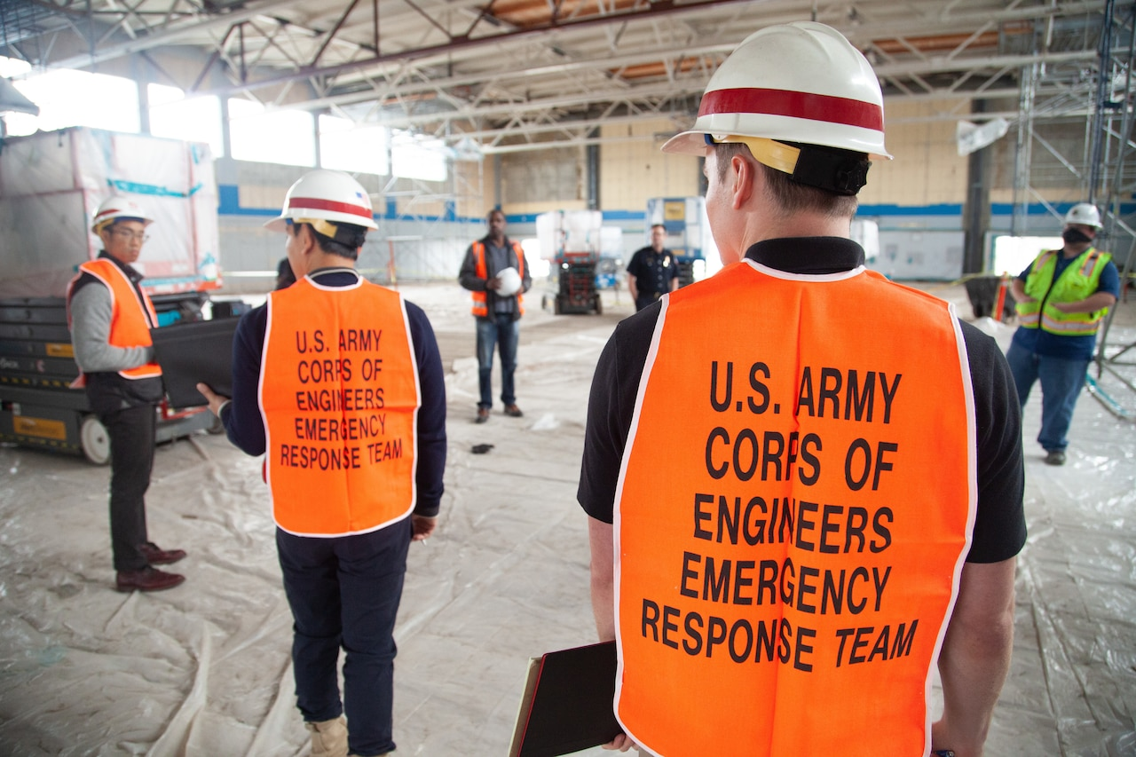 Men in safety gear in a large, empty building.