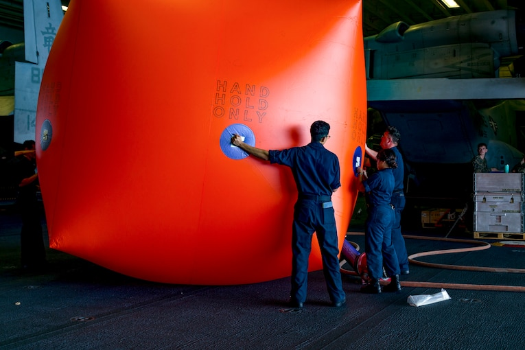Sailors inflate a large orange-ish red target.