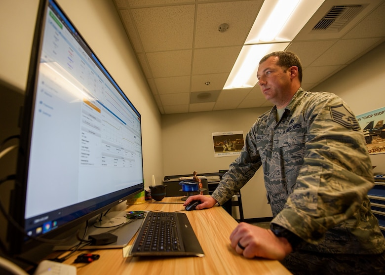 An Airman works on face shield software on a computer.