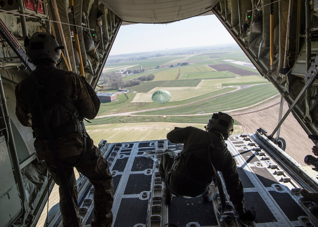 U.S. Air Force Staff Sgt. Brian Clark and Tech. Sgt. Alex Carlson, 37th Airlift Squadron loadmasters, push an airdrop package out over Chievres Air Base, Belgium, March 26, 2020.