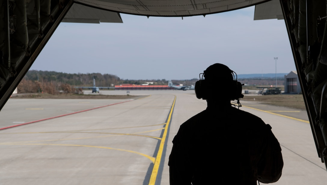 U.S. Air Force Staff Sgt. Brian Clark, 37th Airlift Squadron loadmaster, stares out the back of a C-130J Super Hercules aircraft at Ramstein Air Base, Germany, March 26, 2020.