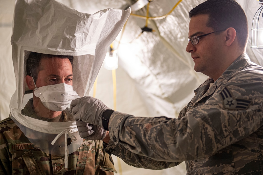 Photo of an Airman performing a protective-mask fit test on another Airman.