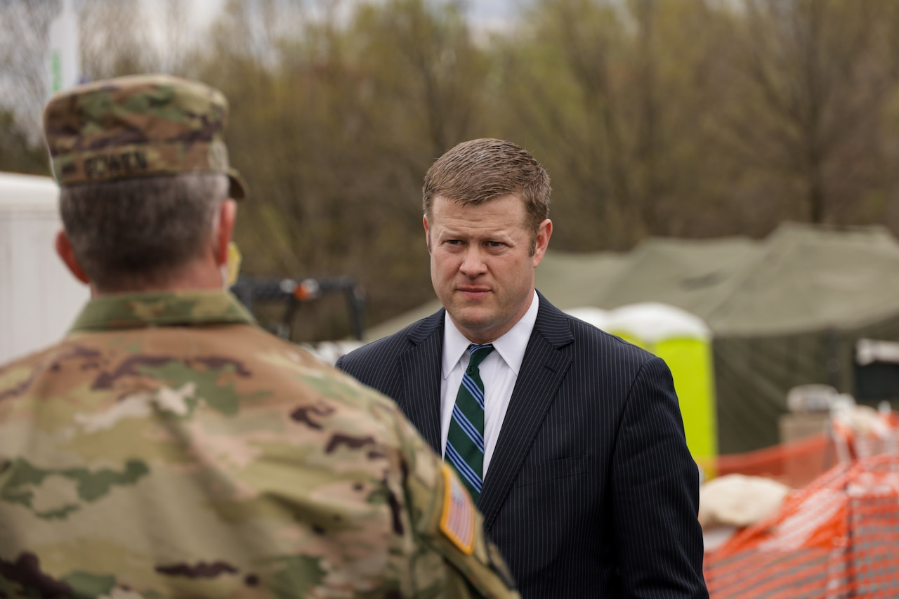 A civilian speaks to a National Guardsman at an outdoor site.
