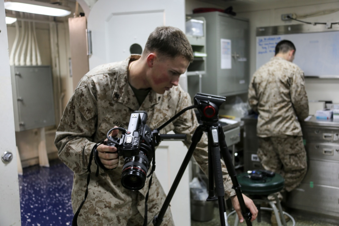 200321-M-OO419-1001 RED SEA (March 21, 2020) Cpl. Gary Jayne III, combat videographer assigned to the 26th Marine Expeditionary Unit (MEU), adjusts a camera tripod aboard the amphibious assault ship USS Bataan (LHD 5) March 21, 2020. Bataan, with embarked 26th MEU, is deployed to the U.S. 5th Fleet area of operations in support of naval operations to ensure maritime stability and security in the Central Region, connecting the Mediterranean and Pacific through the Western Indian Ocean and three strategic choke points. (U.S. Marine Corps photo by Cpl. Nathan Reyes)