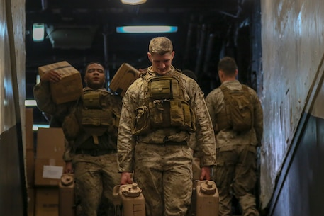 200327-M-IR130-1007 U.S. 5TH FLEET AREA OF OPERATIONS (March 27, 2020) Marines assigned to Weapons Platoon, Fox Company, Battalion Landing Team 2/8, 26th Marine Expeditionary Unit (MEU), carry water containers and meals, ready to eat down the flight ramp of the amphibious assault ship USS Bataan (LHD 5) March 27, 2020. Bataan, with embarked 26th Marine Expeditionary Unit, is deployed to the U.S. 5th Fleet area of operations in support of naval operations to ensure maritime stability and security in the Central Region, connecting the Mediterranean and Pacific through the Western Indian Ocean and three strategic choke points. (U.S. Marine Corps photo by Cpl. Gary Jayne III