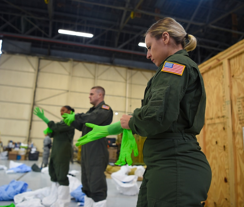 U.S. Air Force Staff Sgt. Laura Mendoza dons her personal protection equipment March 5, 2019, during transportation isolation system training at Joint Base Charleston, S.C. Mendoza is a respiratory therapist from the 60th Surgical Operations Squadron at Travis Air Force Base, Calif. Engineered and implemented after the Ebola virus outbreak in 2014, the TIS is an enclosure the Department of Defense can use to safely transport patients with highly contagious diseases. (U.S. Air Force photo by Senior Airman Cody R. Miller)