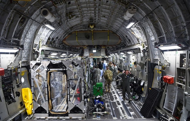 A U.S. Air Force C-17 Globemaster III is prepped to transport a transportation isolation system March 6, 2019, during a training exercise that allows Airmen to practice the most effective and safest form of transportation for patients and their medical professionals. Engineered and implemented after the Ebola virus outbreak in 2014, the TIS is an enclosure the Department of Defense can use to safely transport patients with highly contagious diseases. (U.S. Air Force photo by Senior Airman Cody R. Miller)