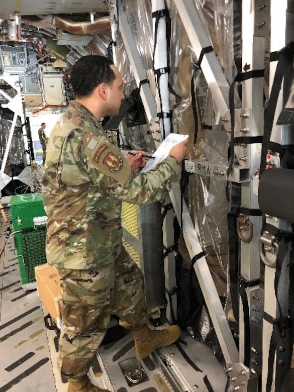 Tech. Sgt. Victor Kipping-Cordoba stands outside a Transport Isolation System (TIS) and provides instruction to an aeromedical evacuation member inside during a training session at Joint Base Charleston March 27, 2020. Kipping-Cordoba and others are training other medical professionals to use the TIS to safely transport patients with highly contagious diseases. (U.S. Air Force photo by Lt. Col. Elizabeth Schnaubelt)