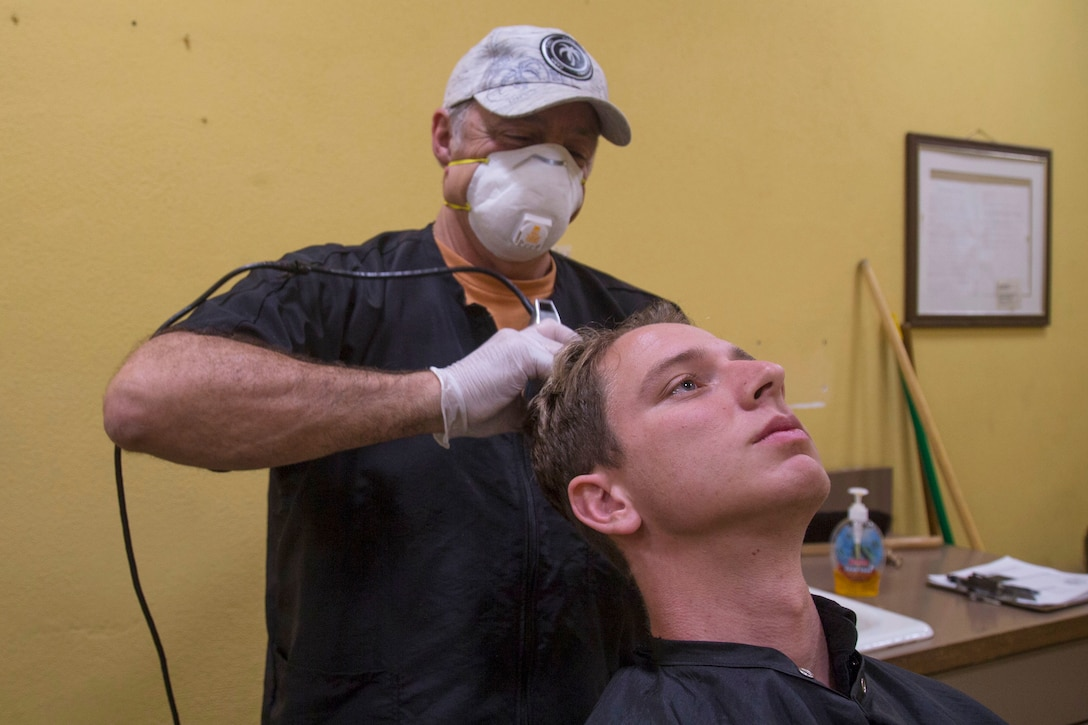 Masked barber gives recruit a haircut.