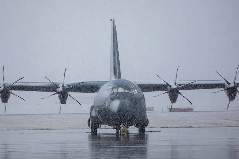 A large military aircraft sits on the tarmac during a snowfall.