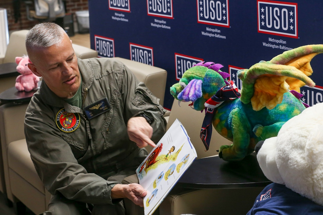 A Marine reads a children's book during a live video feed at the United Service Organization – West aboard MCB Quantico, Va., March 30.