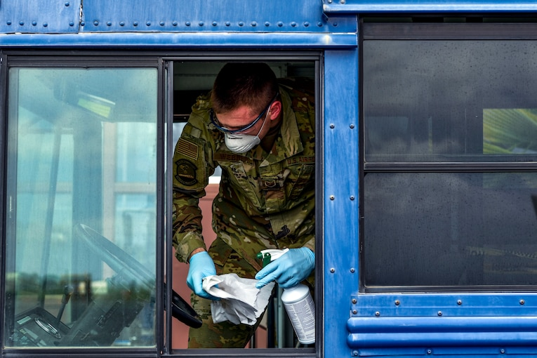 An airman wearing a mask and gloves cleans on a bus.
