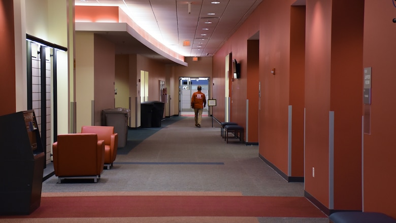 A mission-essential employee walks down a hallway at the U.S. Army Corps of Engineers, Engineering and Support Center, Huntsville