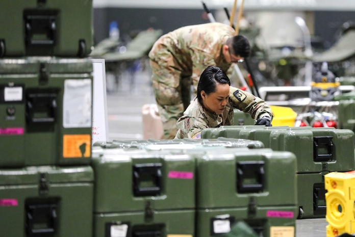A soldier unloads equipment.