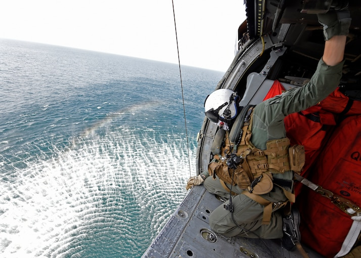 A sailor looks over the side of an open helicopter flying over water.