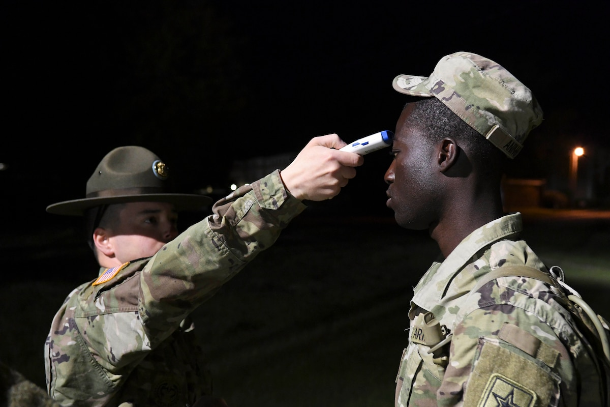 A soldier takes another soldier's temperature.
