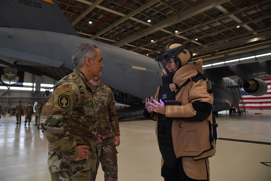 A man speaks to an airman wearing a bomb suit.