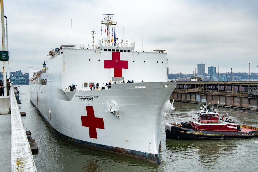 A large white ship with red crosses docks in New York City.