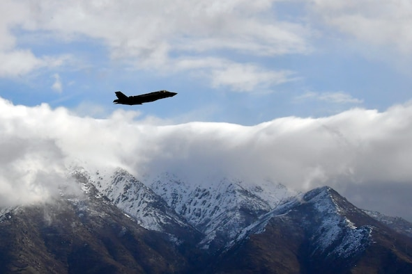 An F-35 takes off near the Wasatch Mountains on a cloudy day