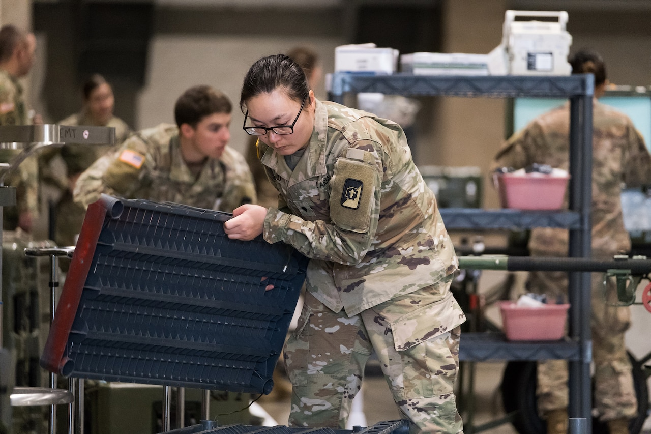 Soldiers build shelving and unload medical equipment.