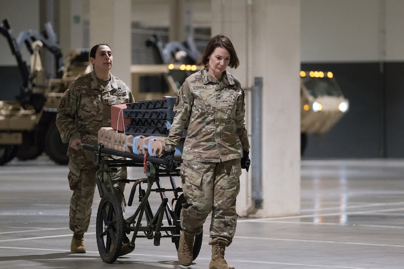 Two soldiers use a gurney to move medical supplies.