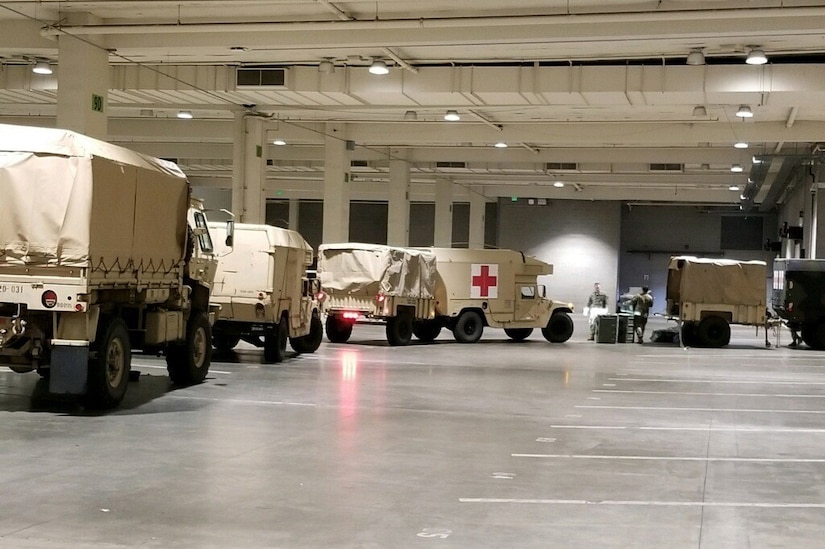 A line of military vehicles, one with a red cross on its side, move through a large garage.