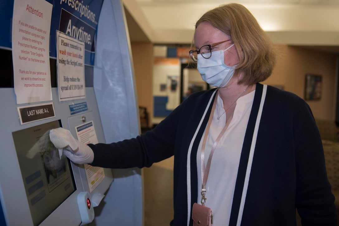 Jacqueline Bradford, 60th Medical Group office assistant, disinfects the prescription refill kiosk March 30, 2020, at Travis Air Force Base, California. Travis AFB pharmacies implemented multiple procedures to combat COVID-19, including wiping down surfaces that are commonly touched by people. (U.S. Air Force photo by Airman 1st Class Cameron Otte)