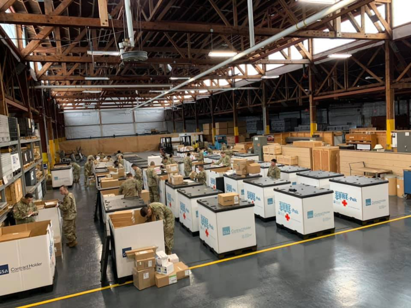 Soldiers from the 551st Medical Company (Logistics) and the 627th Hospital Center unload tri-walls of medical supplies as they arrive at Joint Base Lewis McChord, Washington, in support of COVID-19 relief efforts.
