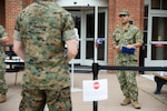 A Navy hospital corpsman asks a patient a series of questions before allowing him to enter the Naval Health Clinic at Marine Corps Base Quantico, Va., March 12, 2020, as a precautionary measure against the coronavirus.