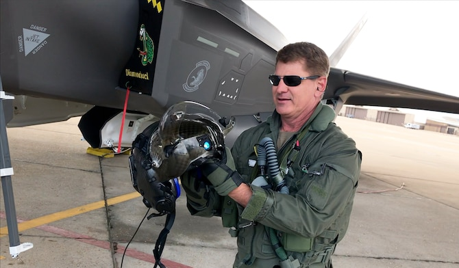 "Col. Brian Silkey, 419th Fighter Wing vice commander, shows off the F-35 helmet to an online audience during a ""virtual field trip"" to Hill Air Force Base, Utah"