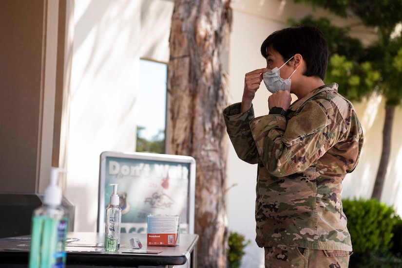 Maj. Aubrey Reid, 30th Medical Group nurse, demonstrates how to properly wear a procedural mask at the 30th MDG COVID-19 screening point March 30, 2020, at Vandenberg Air Force Base, Calif. Prior to entering and when exiting the 30th MDG, each individual is screened for COVID-19 symptoms, such as a cough or a fever. If a member presents any symptoms, they are provided with a mask to help prevent the spread of the virus.  (U.S. Air Force photo by Airman 1st Class Hanah Abercrombie)