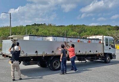 Three associates secure pallets on truck.