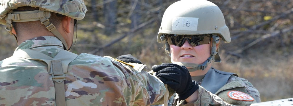 U.S. Army Sgt. Faith Dawson, right, assigned to Task Force Sinai, demonstrates the proper knot for securing a litter onto the back of a Humvee during testing for the Expert Field Medical Badge at the 7th Army Training Command's Grafenwoehr Training Area, Germany, March 29, 2019. To qualify for the badge, Soldiers from U.S. Army Europe, NATO, and other allied and partner nations must complete events such as land navigation, weapons function checks, written tests, medical treatments and evacuations, and a 12 mile ruck march. (U.S. Army photo by Spc. Rolyn Kropf)