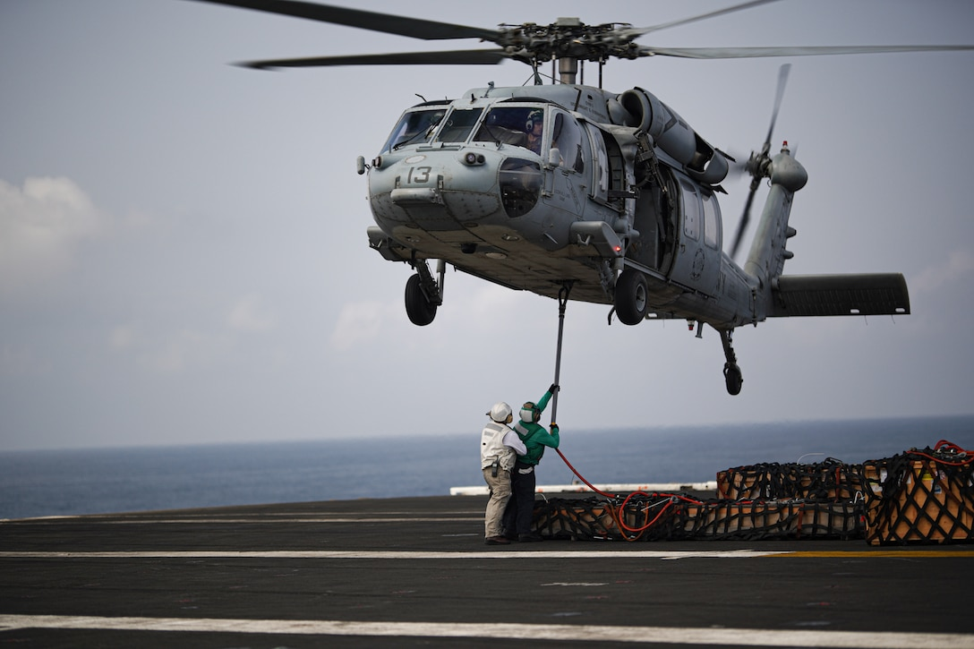 "ARABIAN SEA (April 1, 2020). Chief Ruben Guevara assigned to  the ""Battle Axes"" of Carrier Airwing Three supervisors a Sailor while hooking up a pogo stick to a MH-60S seahawk attached to the ""Dusty Dogs"" of Helicopter Sea Combat Squadron (HSC) Seven while  conducting replenish at sea operations between supply ship USNS Robert E. Peary (T-AKE-5) and aircraft carrier USS Dwight D. Eisenhower (CVN69), April 1, 2020.  Ike is deployed to the U.S. 5th Fleet area of operations in support of naval operations to ensure maritime stability and security in the Central Region, connecting the Mediterranean and Pacific through the Western Indian Ocean and three strategic choke points.  (U.S. Navy photo by PR1 (AW/SW) Brandon C. Cole)"