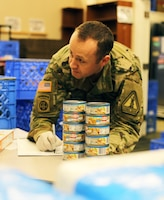 Master Sgt. Dustin McClure, Washington Army National Guard Recruiting and Retention Battalion, inventories canned food at the Issaquah Food Bank in Issaquah, Wash., April 2, 2020. Members of the Washington Air and Army National Guard are supporting food banks around the state during the COVID-19 pandemic.