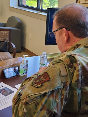 Lt. Gen. Richard Scobee, Air Force Reserve Command commander, uses his cell phone to video chat with one of AFRC's new outstanding Airmen of the year award winners. Since this year's OAY banquet had to be cancelled, senior leaders surprised the winners with teleconferences on April 2. (U.S. Air Force photo by Senior Master Sgt. Virginia Wynn)
