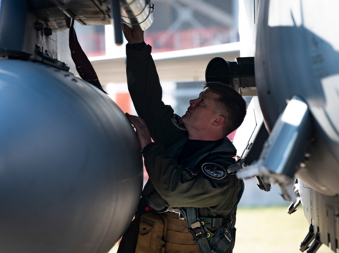 Commander conducts pre-flight checks on his aircraft
