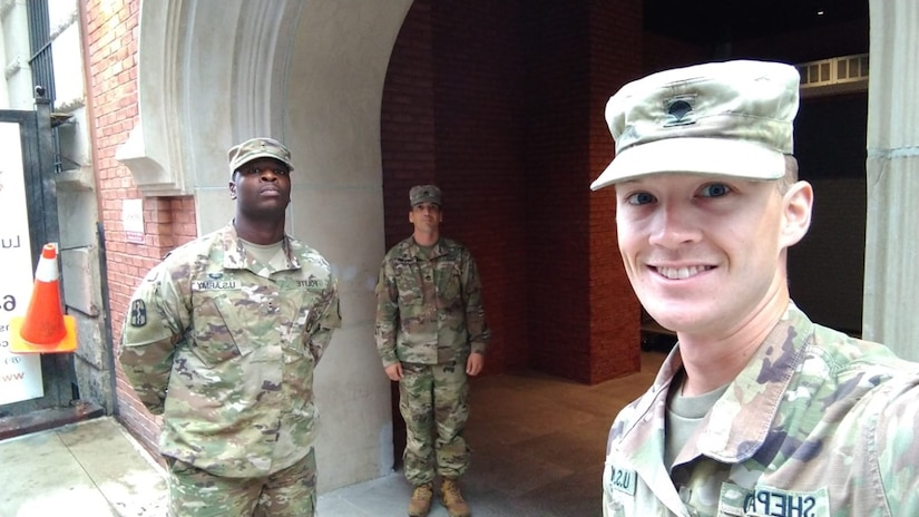 A soldier takes a selfie, while two other soldiers pose far apart in the background.