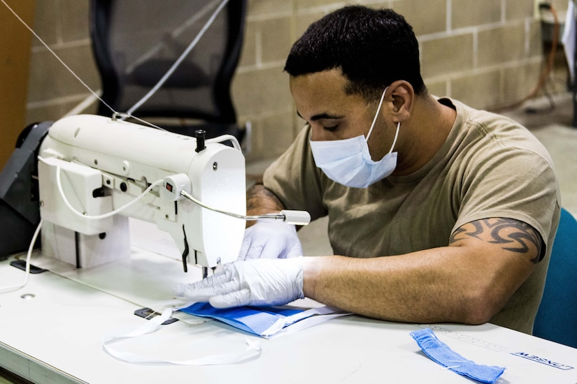 A soldier wearing gloves and a face mask operates a sewing machine.