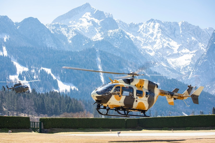 Two helicopters prepare to land with large mountains behind them.