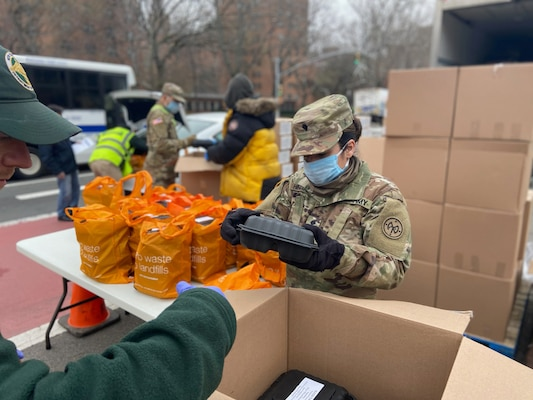 New York Army National Guard Spc. Thalio Hinajosa, assigned to Battery B, 1st Battalion, 258th Field Artillery, part of the 27th Infantry Brigade Combat Team, packs meals for distribution to the community at the Thomas Jefferson Recreation Center in New York City March 30, 2020. Hinajosa is one of more than 2,700 New York Guard members helping mitigate the COVID 19 pandemic.