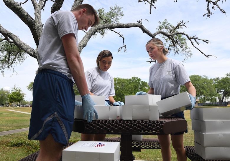 U.S. Air Force Airman 1st Class Seth Haddix, 81st Training Wing public affairs photojournalist; Airman 1st Class Kayle Taylor-Breen, 81st Medical Support Squadron medical logistics technician, and Airman Sofia Mactaggart, 81st Inpatient Operation Squadron medical technician, sort box lunches outside of a lodging building at Keesler Air Force Base, Mississippi, April 3, 2020. Three meals are delivered daily to Keesler personnel that are in 14-day quarantine/isolation, which are being housed inside a select number of lodging buildings in the same area called Comfort Cove. Keesler is taking precautionary measures across the base to reduce the chances our personnel contract or spread the disease. (U.S. Air Force photo by Kemberly Groue)