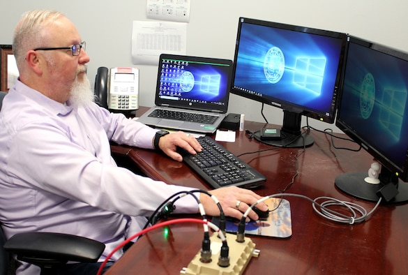 Chris Carr, an AEDC Instrumentation, Data and Controls engineer, demonstrates how the Cross-Domain Solution, or CDS, works Feb. 12, 2020, at Arnold Air Force Base, Tenn. The CDS interface was researched as a solution to allow plant operations systems outside of the plant control room to remain unclassified during classified test programs. As part of an AEDC Innovation Grant project, Carr and several AEDC team members worked together to determine whether plant control parameters could be normalized with the addition of a CDS. (U.S. Air Force photo by Deidre Moon) (This image has been altered by obscuring items for security purposes.)