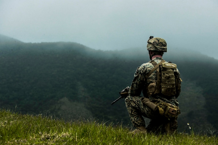 A Marine kneels on a grassy hill.