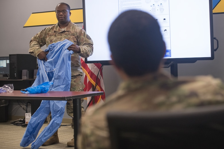 Staff Sgt. Myren Richardson, 437th Maintenance Group aircraft maintenance instructor, teaches students how to put on and remove personal protective equipment during a C-17 COVID-19 Decontamination Course at Joint Base Charleston, S.C., April 2, 2020. Members of the 437th MXG began implementation of the course March 28, 2020 to help ensure the safety of maintainers, aerial port personnel, aircrew and passengers while continuing support of Air Mobility Command's rapid global mobility mission during the global pandemic.