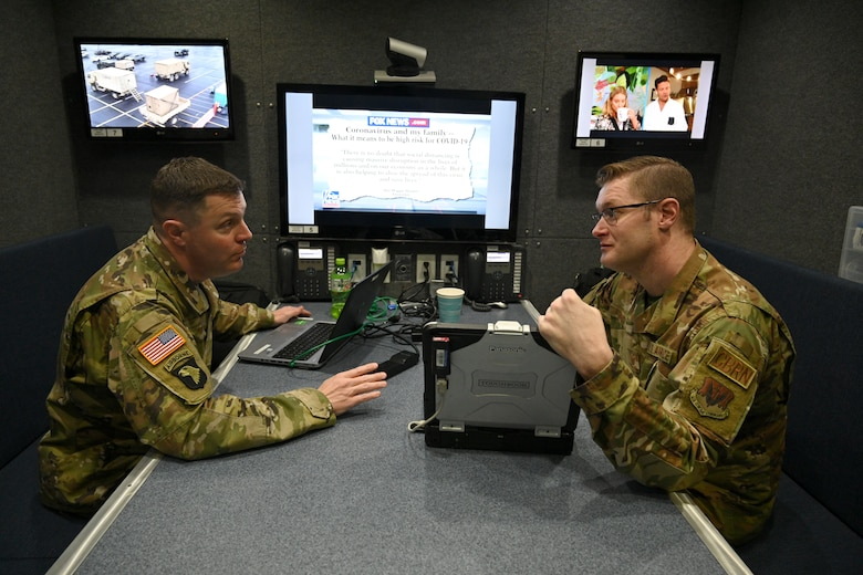 U.S Air Force Tech. Sgt. Derek White (right), an emergency manager assigned to the 175th Emergency Management Flight, Maryland Air National Guard, and Army Sgt. First Class Timothy Ryan, a battalion logistics non-commissioned officer assigned to the 115th Military Police Battalion, Maryland Army National Guard, discuss security and communication strategies while deployed to FedEx Field in support of Prince George's County Department of Health's efforts to set up a COVID-19 medical screening center in Landover, Maryland. The 175th Wing Emergency Management Unit is the first Air National Guard unit to respond nationally providing support with its Mobile Emergency Operations Center to set up a COVID-19 temporary testing facility. (U.S. Air Force photo by Staff Sgt. Enjoli Saunders)