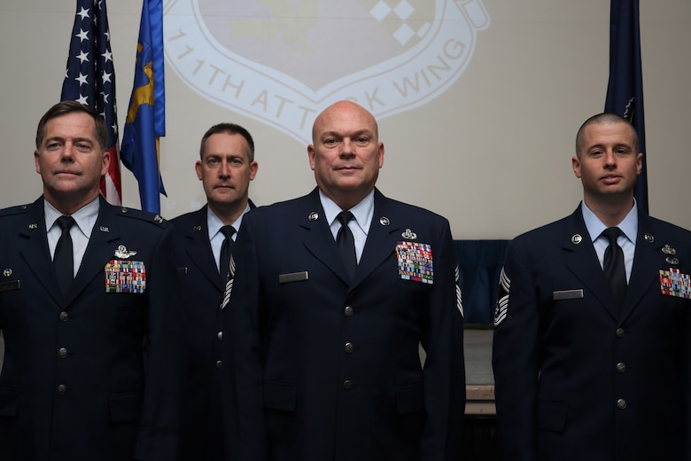 Four airmen in dress blue uniform stand at attention.