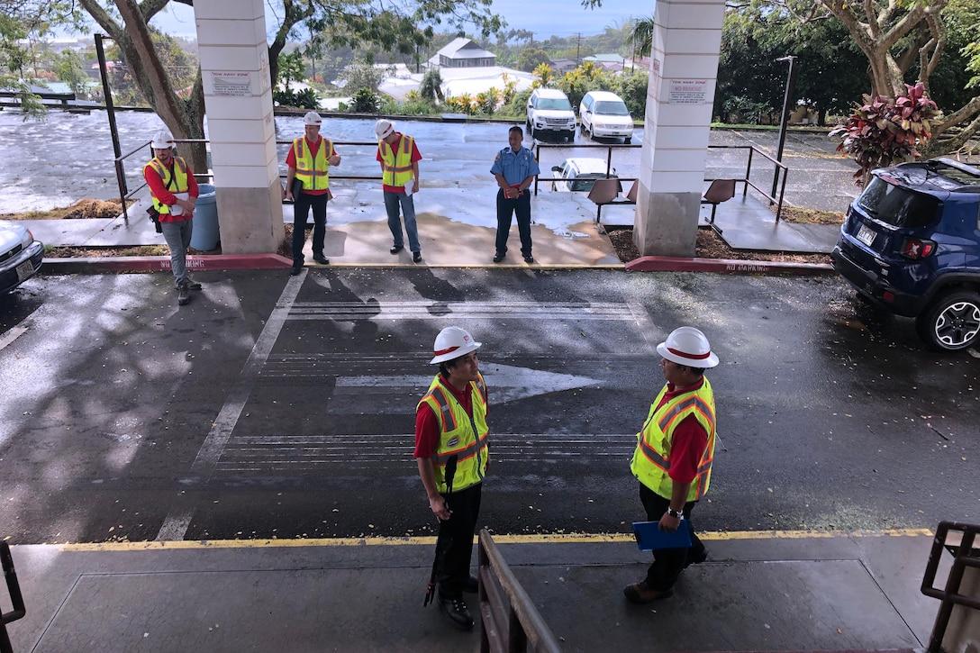 Construction team surveys space.